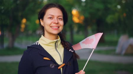 canadian maple leaf : Slow motion portrait of attractive girl Canadian sports fan holding national flag of Canada and looking at camera with smile. People and countries concept. Stock Footage