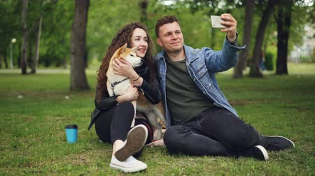 pies : Handsome young man is taking selfie with his girlfriend who is holding pedigree dog, guy is kissing girl then watching photos on screen, people are laughing.