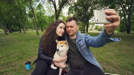 tomar : Cheerful guy is taking selfie holding smartphone and kissing his wife while she is holding adorable dog and kissing it. Relationship, love, romance and technology concept.