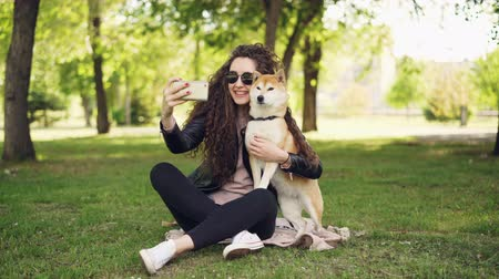 acariciando : Cheerful blogger pet owner is taking selfie with her dog using smartphone, human and animal are sitting on lawn in the park and posing, woman is caressing and kissing dog.