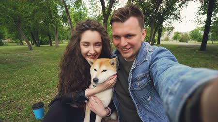 tomar : Young wife and husband are taking selfie with adorable dog kissing and hugging each other and the animal. Point of view shot of happy people, pet and green park. Stock Footage