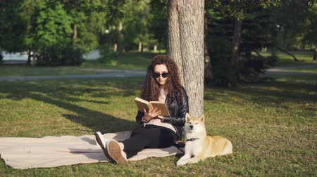 okuyucu : Attractive girl student is reading book sitting on plaid under tree in city park with her puppy lying near and enjoying sunlight. Hobby, leisure and animals concept.