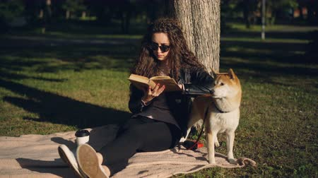 enciclopédia : Beautiful young woman is reading book sitting on blanket under tree in park and smiling while her pedigree dog is standing near her enjoying nature. Stock Footage