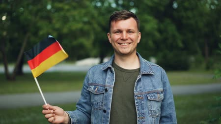 activist : Slow motion portrait of cheerful German tourist waving official flag of Germany, smiling and looking at camera. Nice park is in background, warm summer day.