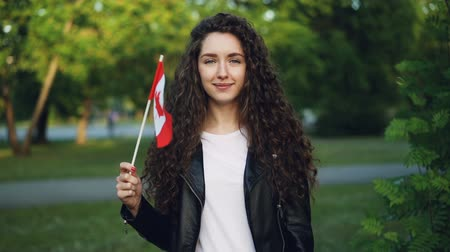 canadian maple leaf : Slow motion portrait of happy Canadian sports fan waving national flag of Canada looking at camera with glad smile while standing outside in park on summer day. Stock Footage