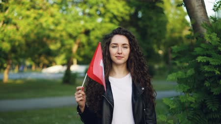 гордый : Slow motion portrait of attractive young woman proud Swiss citizen waving national flag of Switzerland, looking at camera and smiling. Countries and nationalities concept. Стоковые видеозаписи