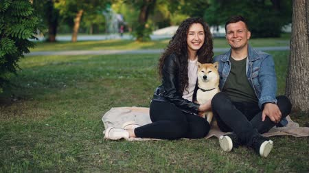 небрежный : Slow motion portrait of adorable couple and pedigree dog sitting on blanket on grass in the park, looking at camera and smiling. Nature and family concept.