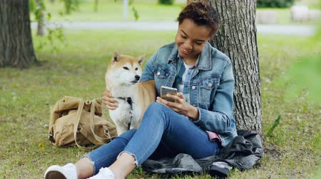 patting : Sociable girl is using smartphone texting friends and stroking her adorable puppy while resting in park at weekend. Modern technology, people and animals concept.