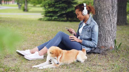 芝 : Attractive African American woman is listening to music with headphones and using smartphone sitting on grass in park while her dog is lying nearby eating grass. 動画素材