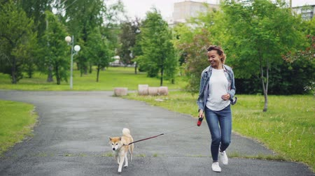 вести : Slow motion of happy mixed race girl running in city park with beautiful small dog enjoying nature, freedom and outdoor activity. Healthy lifestyle concept.
