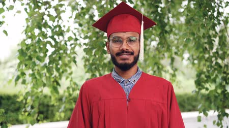 master's degree : Portrait of bearded mixed race man graduating student in gown and mortar-board smiling and looking at camera standing outdoors on campus. People and education concept. Stock Footage