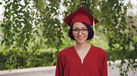 glass master : Portrait of joyful young woman graduating student in gown and mortar-board smiling and looking at camera standing under the tree on campus. Youth and education concept.