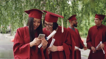 diplom : Female graduates are using smartphone looking at screen talking and laughing standing outdoors holding diplomas, girls are wearing formal gowns and hats.
