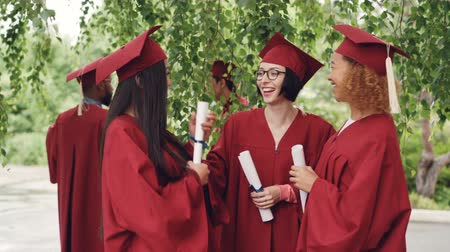umutlu : Fellow students are talking and laughing after graduation ceremony holding diplomae and wearing gowns and mortarboards, girls are sharing memories and expressing hopes.