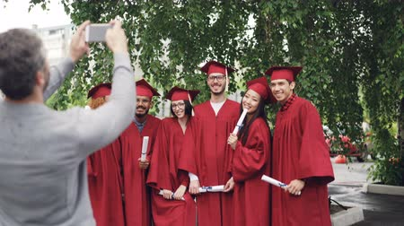 гордый : Proud father is taking pictures of graduating students with smartphone while young people are posing, waving hands with diplomas and gesturing. Technology and education concept. Стоковые видеозаписи