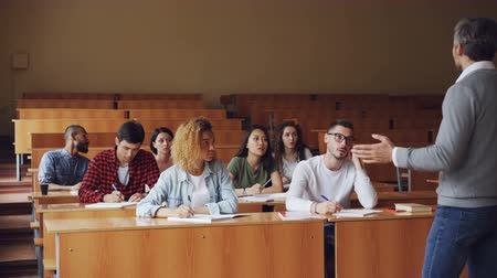 mais alto : Tutor is talking to students sitting at desks in spacious college lecture hall, young people in casual clothes are asking questions. Education and university concept. Vídeos