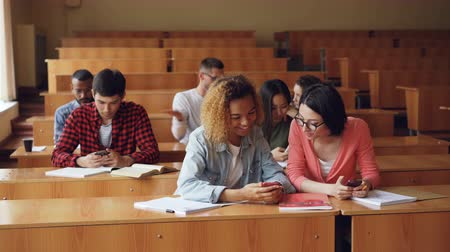 participants : Cheerful students are using smartphones and chatting during break between lectures at university. Modern technology, youth and education concept. Stock Footage