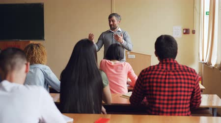 conference table : Schoolboy is raising hand and answering teachers question while educator is checking knowledge standing in front of students desk. Schools and people concept.