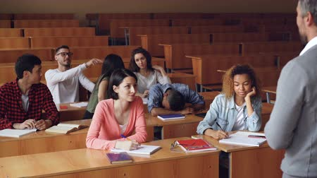 higher : Tired mixed race student is sleeping during lecture at college, his classmates are waking him up, he is standing and talking to teacher, young people are laughing.