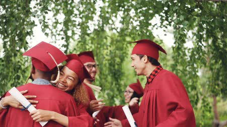 bakalář : Happy graduating students multi-ethnic group is hugging and doing high-five after graduation ceremony, girls and guys in mortar-boards and gowns are laughing and having fun.