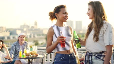 socializing : Happy young women are chatting, clinking bottles and drinking standing on rooftop with their friends having fun in background. Millennials, joy and summer concept. Stock Footage