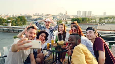 alma : Happy young men and women are taking selfie with smart phone posing, laughing and making hand gestures celebrating holiday on roof at table with food and drinks.