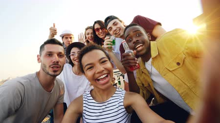 smíšené rasy osoba : Point of view shot of African American girl holding camera and taking selfie with happy friends at party on roof. Men and women are looking at camera, posing and laughing.