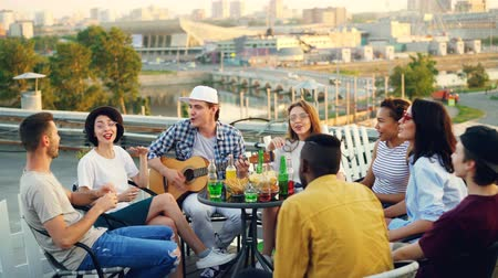 guitarrista : Young people are having fun on rooftop playing the guitar, singing, chatting and laughing sitting at table outdoors. Joy, music, youth and friendship concept.
