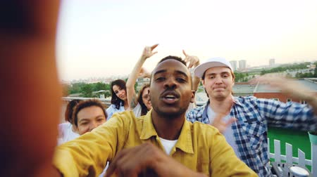 friendship dance : Point of view shot of African American man vlogger recording video for his blog about party with friends on rooftop, people are looking at camera, dancing and talking.