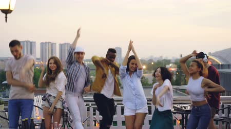 friendship dance : Sad people are standing on rooftop and looking at camera then starting dancing and jumping having fun with happy faces while DJ is working with mixing console. Stock Footage