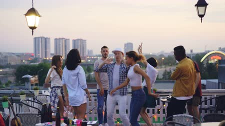 friendship dance : Multiracial group of friends is dancing on rooftop having cool party with DJ in the evening in summer. Joyful youth, entertainment and big city concept. Stock Footage
