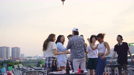 friendship dance : Professional DJ is working at cool rooftop party with joyful young men and women dancing and having fun enjoying music, leisure and summertime.
