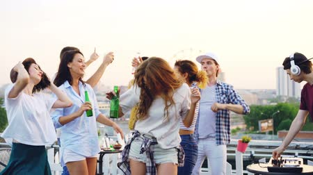friendship dance : Slow motion of attractive girls and guys students dancing at open-air party with professional DJ working with digital mixer. Friends are holding bottles and having fun.