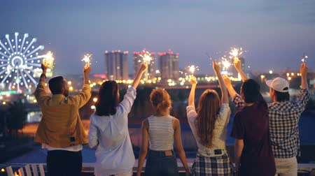 kabarık : Slow motion of happy youth friends holding sparklers and moving raised hands standing on rooftop enjoying beautiful view of big city. Friendship, fun and nightlife concept.