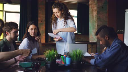 small group : Confident young woman director is giving documents to her employees and talking to group of people sitting at desk in office. Paperwork, planning and youth concept. Stock Footage