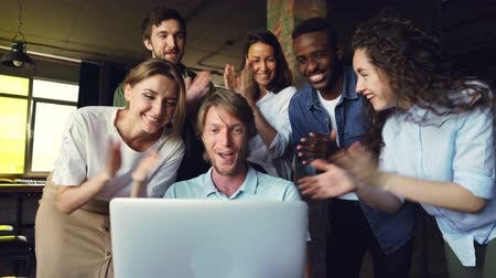 victorious : Excited young man is looking at laptop screen, rejoicing and expressing happiness, his colleagues are congratulating him on success clapping hands and touching shoulder.