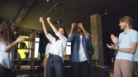 victorious : Caucasian and African American young people coworkers are dancing at office party having fun and clapping hands. Modern youth, corporate culture and holidays concept.