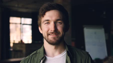 wąsy : Close-up slow motion portrait of happy bearded guy with dark hair standing in modern office, looking at camera and smiling. People, work and career concept.