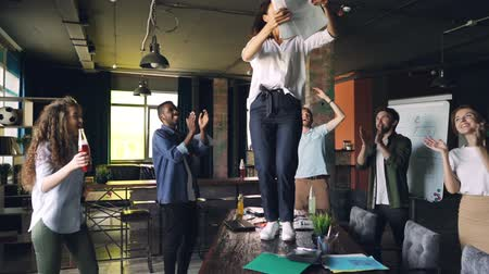 victorious : Clow motion of joyful young lady dancing on table at office party with pile of paper and throwing documents while her team is laughing and dancing around her.