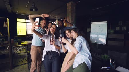 tomar : Slow motion of multi-ethnic team taking selfie with drinks at corporate party using smartphone. Men and women are celebrating holiday together and having fun.
