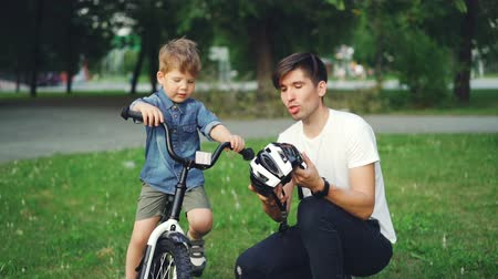 biztonság : Caring father is holding bicycle helmet and talking to his adorable son explaining safety regulations while boy is sitting on bike, smiling and listening to dad.