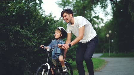 öğrenme : Slow motion of happy young man loving father teaching his child to cycle in green park in summer, little boy is laughing, shouting and enjoying weekend with dad. Stok Video