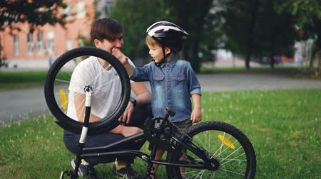 zvědavý : Curious child wearing helmet is spinning bicycle wheel and pedals while his father is talking to him on lawn in park on summer day. Family, leisure and active lifestyle concept.