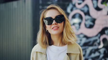 carelessness : Portrait of beautiful blond girl in sunglasses looking at camera, laughing and touching her hair standing outdoors. Youth, fashion and emotions concept.