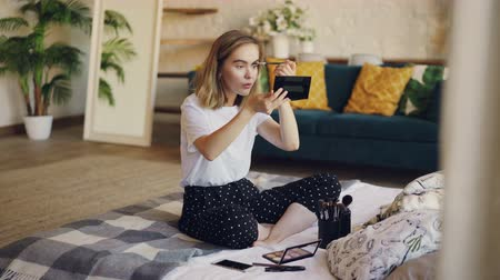 dokonalost : Good-looking girl is using cosmetics to paint eyebrows, she is holding brush and applying make-up looking at mirror. Beauty, people and apartments concept.