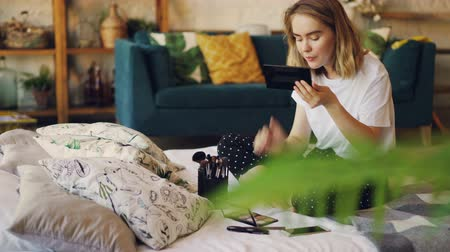 dokonalost : Beautiful blonde is painting lips putting on make-up using professional decorative cosmetics sitting on bed at home. Beauty, interiors and young women concept.