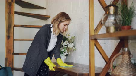 servant : Blond housewife wearing protective rubber gloves is dusting a table at home doing housework. Headphones, staircase and beautiful wooden furniture is visible.