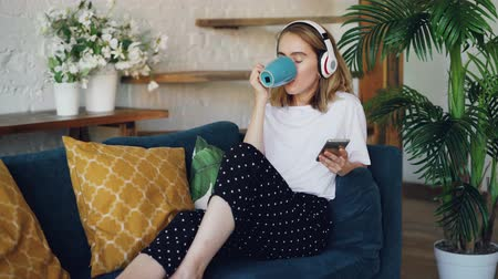 wi fi : Modern young woman is resting on comfortable sofa at home with smartphone, cup of tea and headphones. Girl is listening to music, singing and enjoying drink.