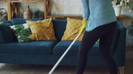dweilen : Creative housekeeper is mopping the floor and enjoying music in headphones singing in mop and dancing barefoot on clean wooden floor. Technology and occupation concept. Stockvideo