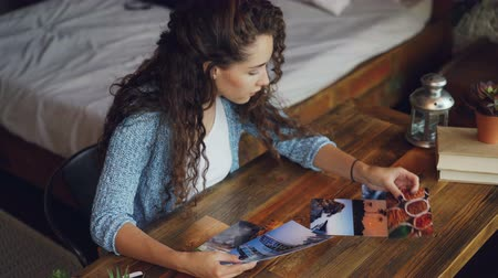 projektant : Female photographer is looking at photographs sitting at table and putting pictures on wooden desk. Loft style apartment with modern furniture is visible. Wideo